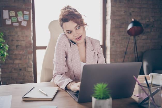 Closeup retrato de um celular focado em uma senhora bem-sucedida conversando com um laptop de trabalho