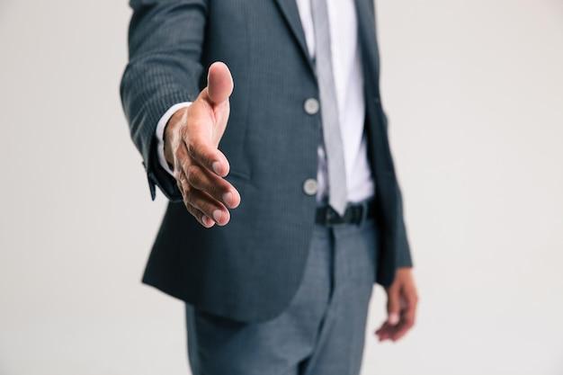 Closeup retrato de um empresário esticando a mão para um aperto de mão isolado