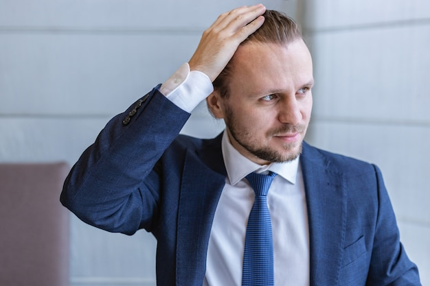 Closeup retrato de um homem de terno a desviar o olhar e tocar-se a cabeça