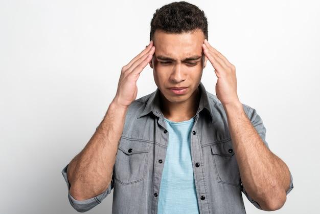 Closeup retrato de um homem mulato, segurando sua cabeça, dor de cabeça ou muito chateado
