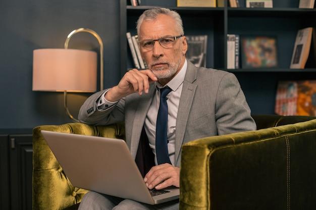Closeup retrato de um homem sério e bonito de cabelos grisalhos sentado com um laptop olhando para a frente
