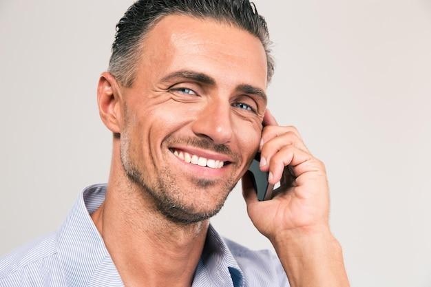 Closeup retrato de um homem sorridente, falando ao telefone isolado. olhando para a câmera