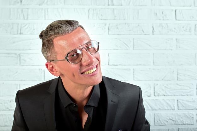 Closeup retrato de um jovem empresário feliz usando óculos e um terno preto, olhando para a câmera em um fundo branco