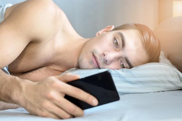 Closeup retrato de um jovem, olha mensagens em um smartphone na cama em casa de manhã
