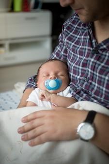 Closeup retrato de um lindo menino adormeceu nas mãos do pai