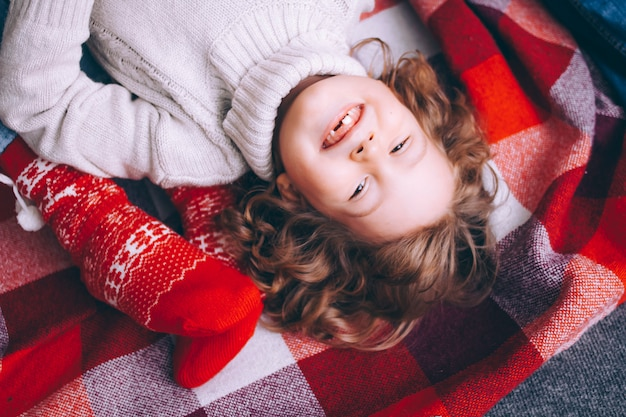 Closeup retrato de um menino de cabelos cacheados, o menino encontra-se em uma manta vermelha no chão com um suéter sorrindo sem dentes, olhando para o quadro.