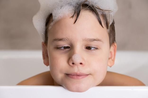 Closeup retrato de um menino engraçado brincando com água e espuma no banheiro bonito criança feliz banhar-se