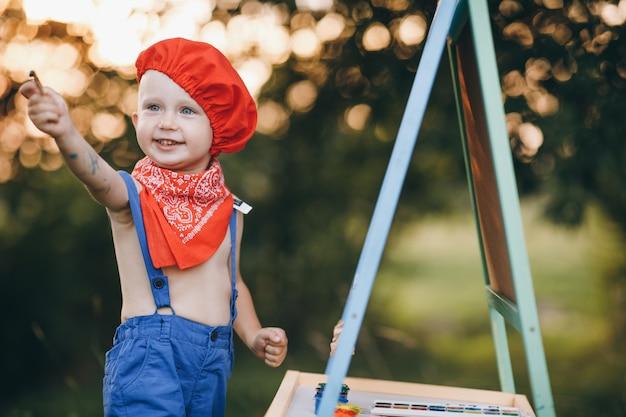 Closeup retrato de um menino que sorri com vergonha e se alegra com a tinta nas mãos ao pôr do sol