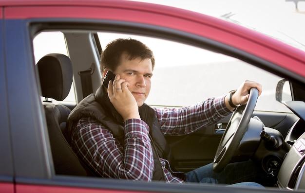 Closeup retrato de um motorista falando ao telefone enquanto dirige um carro