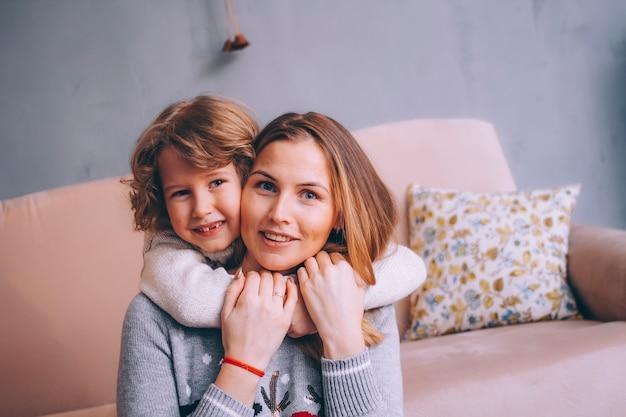 Closeup retrato de um pequeno filho e mãe. filho abraça a mãe pelo pescoço. mãe e filho estão olhando para o quadro e sorrindo.