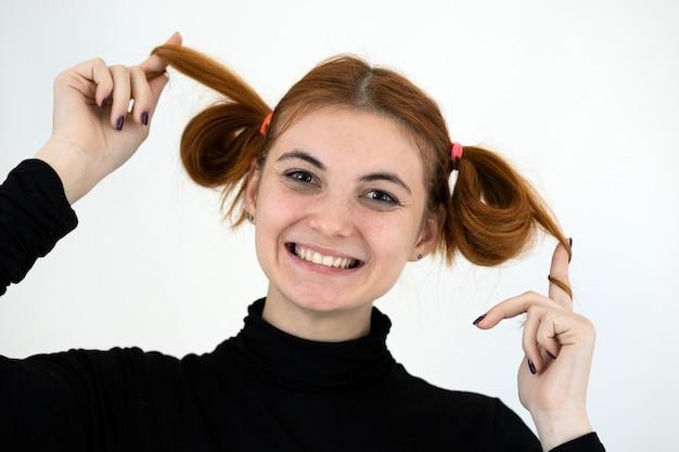 Closeup retrato de uma adolescente ruiva engraçada com penteado infantil sorrindo felizmente isolado no fundo branco.