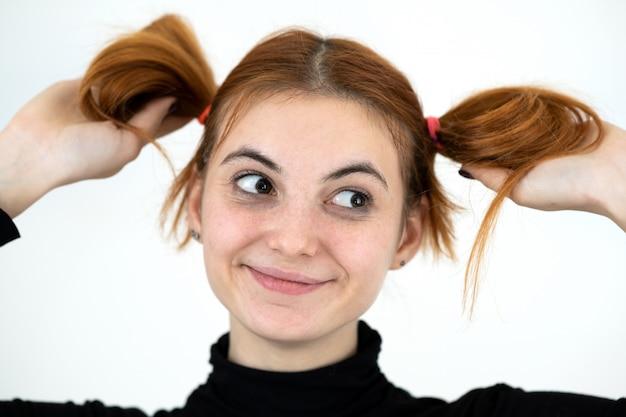 Closeup retrato de uma adolescente ruiva engraçada com penteado infantil