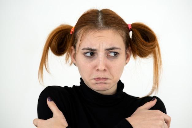 Closeup retrato de uma adolescente ruiva triste com um penteado infantil e parecendo ofendida