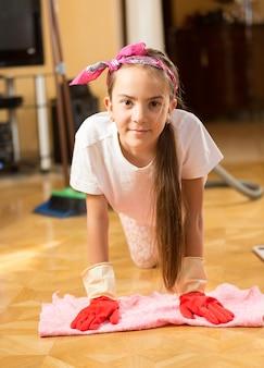 Closeup retrato de uma adolescente sorridente lavando o chão com um pano
