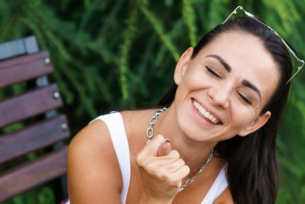 Closeup retrato de uma alegre mulher caucasiana mostra um doo e sorri com os olhos fechados, sentado em um ...