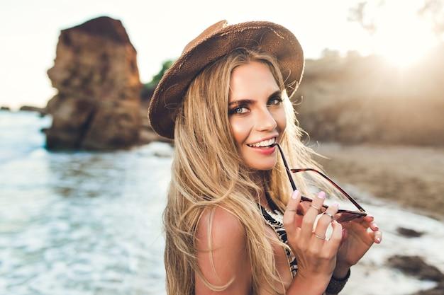 Closeup retrato de uma atraente garota loira com cabelo comprido, posando na praia rochosa. sshe segura os óculos escuros e sorri para a câmera.