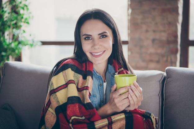 Closeup retrato de uma bela atraente adorável fofa alegre morena sentada no divã coberto aconchegante xadrez bebendo chá verde quente e passar um tempo em segurança moderno loft apartamento de casa industrial de tijolo