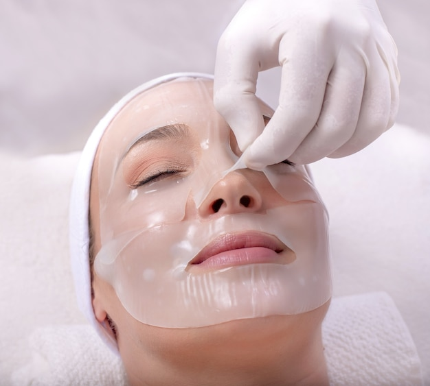 Closeup retrato de uma bela jovem caucasiana aplicando máscara facial