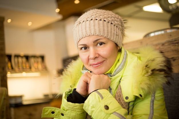 Closeup retrato de uma bela mulher de meia-idade sentada em um café no topo de uma montanha