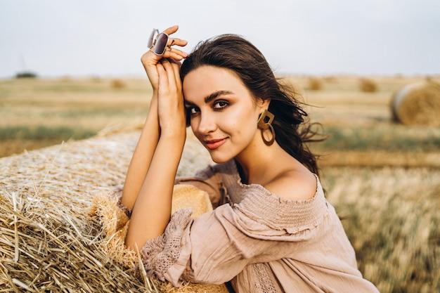 Closeup retrato de uma bela mulher sorridente com os olhos fechados. a morena inclinou-se sobre um fardo de feno. um campo de trigo