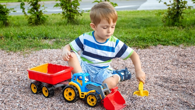Closeup retrato de uma criança de 3 anos sorridente e feliz, cavando areia no parquinho com um caminhão de brinquedo de plástico ou escavadeira