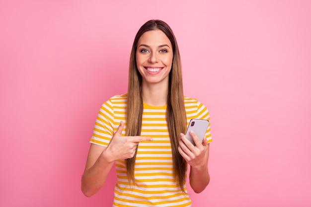Closeup retrato de uma garota alegre e confiante demonstrando o telefone com o dedo