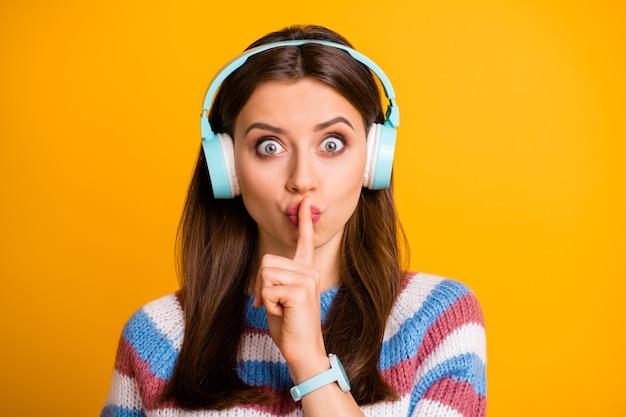 Closeup retrato de uma garota atraente e preocupada ouvindo uma música mostrando o sinal de shh