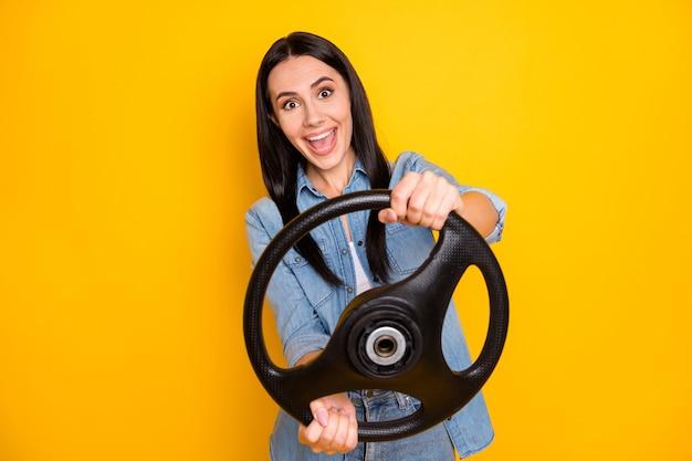Closeup retrato de uma garota engraçada segurando nas mãos o volante se divertindo