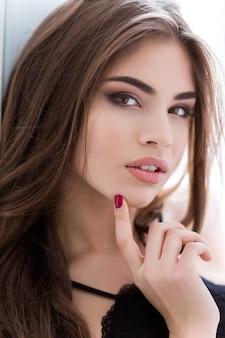 Closeup retrato de uma jovem atraente com cabelo comprido, olhando para a câmera