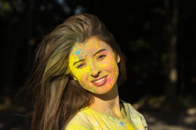 Closeup retrato de uma jovem bonita posando com pó de holi no rosto e pescoço