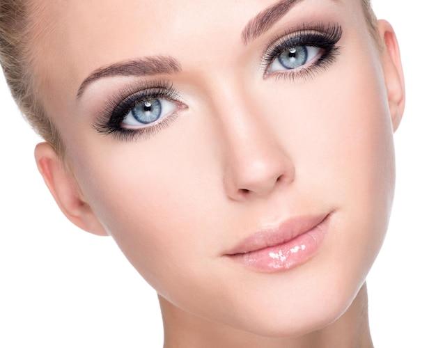 Closeup retrato de uma jovem e bela mulher branca com longos cílios postiços sobre uma parede branca
