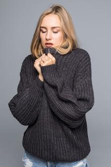 Closeup retrato de uma jovem feliz em uma roupa quente de inverno em fundo cinza