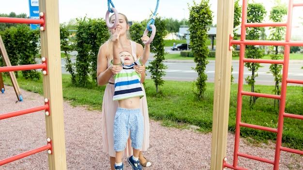 Closeup retrato de uma jovem mãe ajudando e segurando seu filho pendurado e balançando em anéis sportrs em palyground