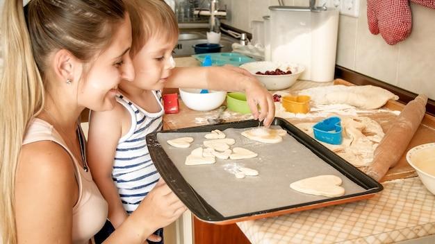 Closeup retrato de uma jovem mãe com um filho pequeno segurando uma assadeira e fazendo biscoitos na cozinha