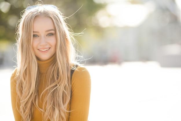 Closeup retrato de uma jovem mulher atraente ao ar livre com espaço de cópia. modelo linda loira. ladyin alegre primavera, outono, outono.