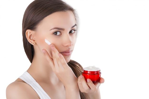 Closeup retrato de uma jovem mulher atraente, aplicar creme para o rosto. mulher segurando um frasco com creme hidratante para o rosto.