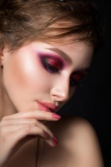 Closeup retrato de uma jovem mulher bonita com olhos esfumados rosa brilhantes. menina tocando seus lábios. maquiagem da moda. tiro do estúdio. maquiagem de verão moderna