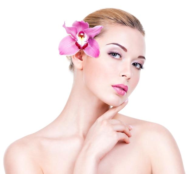 Closeup retrato de uma jovem mulher bonita com uma pele limpa e saudável do rosto. menina muito adulta com uma flor perto do rosto. - isolado na parede branca