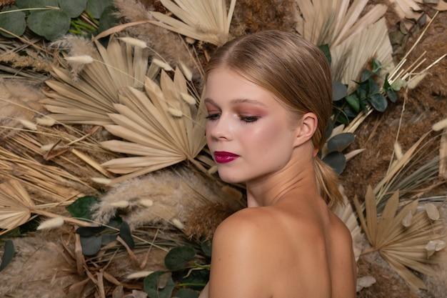 Closeup retrato de uma jovem mulher bonita com uma pele saudável do rosto. fica de costas e olha para baixo menina loira com lábios cor de vinho contra um fundo de flores secas da primavera.