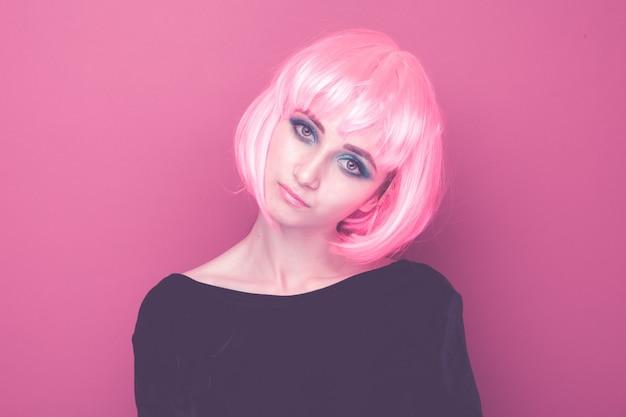 Closeup retrato de uma jovem mulher bonita no estilo dos anos 90 em peruca rosa standin isolado em um estúdio brilhante.