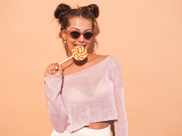 Closeup retrato de uma jovem mulher bonita sexy sorridente com penteado ghoul. menina na moda em roupas de verão casual em óculos de sol. modelo quente isolado em bege. comendo, mordendo pirulito doce