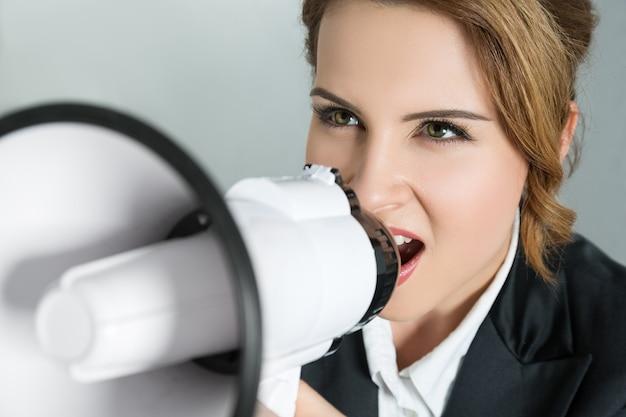 Closeup retrato de uma jovem mulher de negócios gritando com um megafone