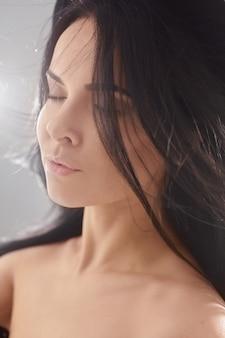 Closeup retrato de uma jovem mulher satisfeita com maquiagem nude e cabelos negros esvoaçantes, vestindo uma árvore ...