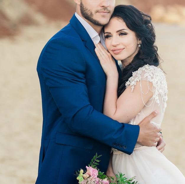 Closeup retrato de uma jovem noiva e do noivo com buquê posando perto da antiga catedral. casal em lua de mel se beijando no dia do casamento, casal feliz apaixonado, beijo de casamento