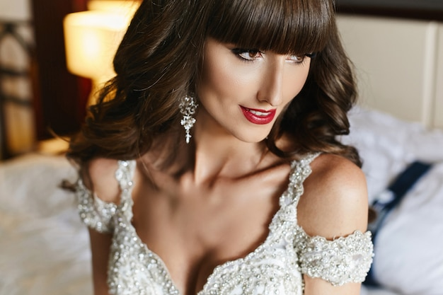 Closeup retrato de uma jovem noiva linda com penteado de casamento e lábios vermelhos em vestido de noiva. jovem mulher em um vestido de noiva de luxo decorado com cristais. moda casamento