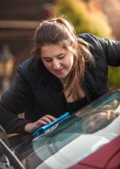Closeup retrato de uma jovem polindo o pára-brisa