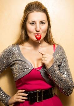 Closeup retrato de uma jovem sexy beijando um coração vermelho decorativo