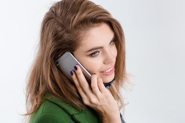 Closeup retrato de uma jovem sorridente falando ao telefone, isolado em um fundo branco