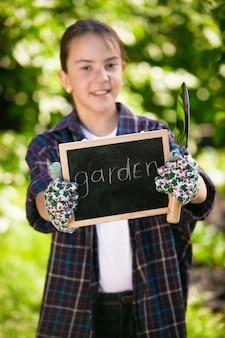 Closeup retrato de uma linda garota em luvas de jardinagem, segurando uma lousa e ferramentas