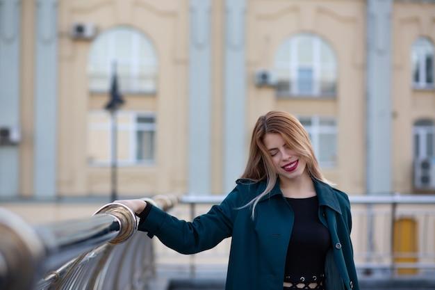 Closeup retrato de uma linda garota loira de casaco verde segurando no trilho. espaço para texto
